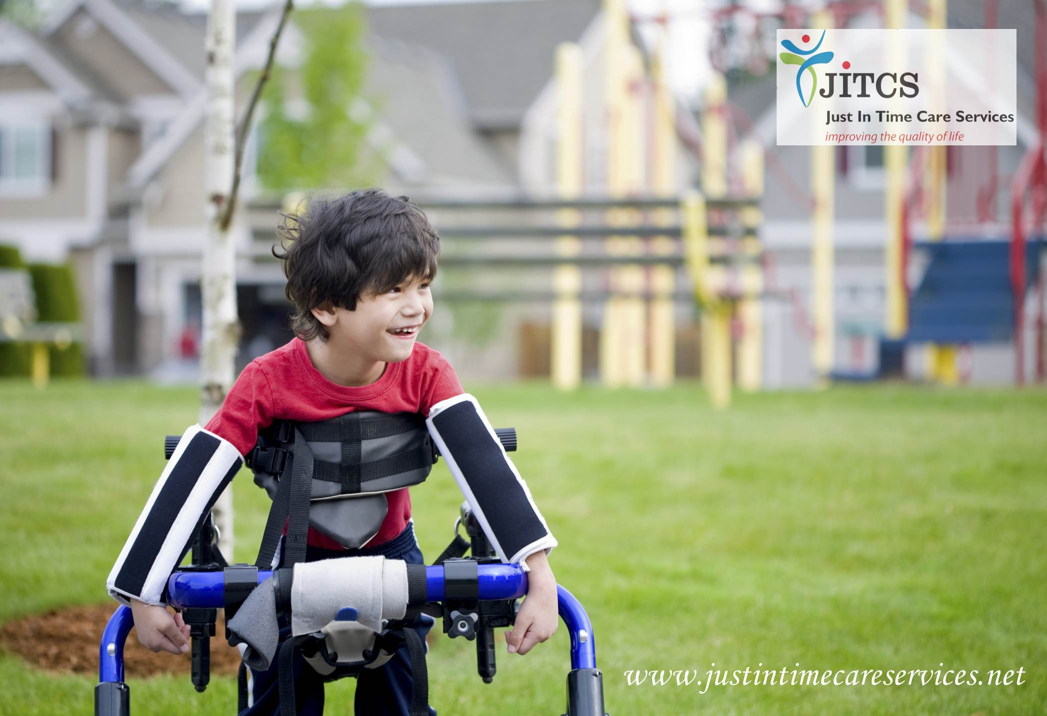 Disabled four year old boy standing in walker by playground